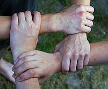 Vier Menschen demonstrieren Zusammenhalt durch gemeinsamen Händedruck